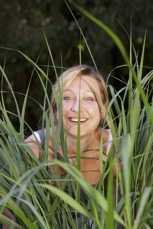 Young blond woman looking through reed Stock Photo - 21597109