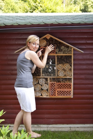 Young blond woman showing insect hotel Stock Photo - 21622050