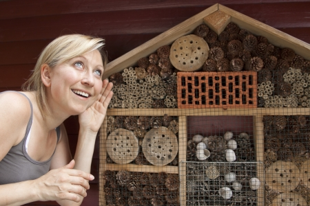 blond woman showing insect hotel Stock Photo - 21622051