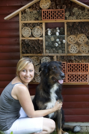 blond woman with dog showing insect hotel Stock Photo - 21622052