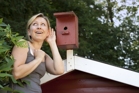 Young blond woman listening to bird house Stock Photo - 21622054