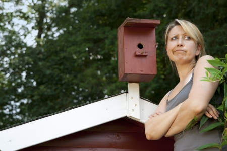 Woman at Birdhouse is worried Stock Photo - 21622056
