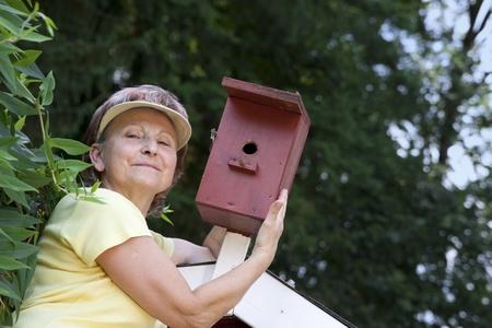 senior woman in the garden at the bird feeder Stock Photo - 21622057