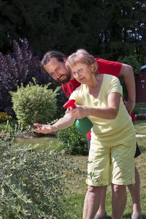 Man watches senior woman at gardening photo