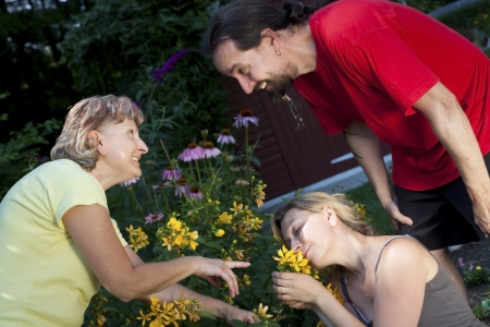 senior woman showing a couple flowers in the garden photo