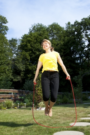 pretty woman jumping rope in the garden photo