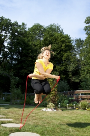 Athletic blond woman jumping rope in the garden photo