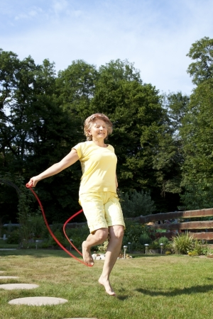 Mature woman has fun with jumping rope photo