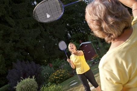 Two women playing badminton in the garden Stock Photo - 21622082