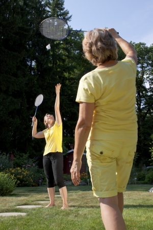 Two women are playing badminton in the garden photo