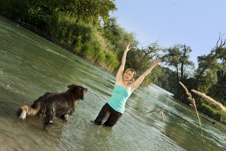 pretty woman playing with dog in water Stock Photo - 21622150