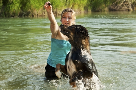 Dog and young woman are playing in water photo