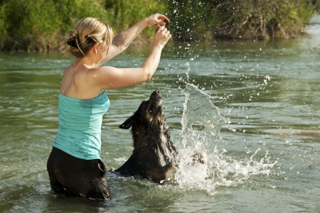 pretty woman in water animated dog to play Stock Photo - 21622153