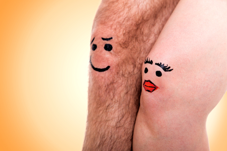 two knees with faces in front of yellow background photo