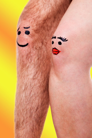 two knees with funny faces in front of yellow background photo