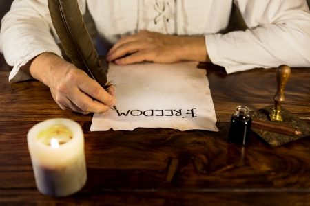 declaration: Man is writing on parchment freedom Stock Photo