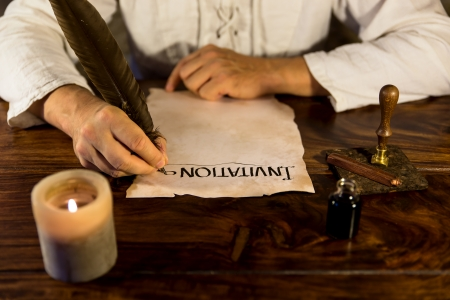 Man is writing on a parchment Invitation photo