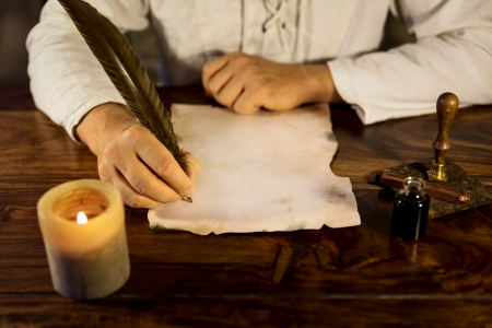 man writing on a old parchment photo