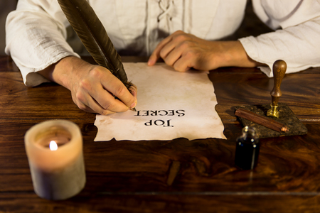 old writing: Man is writing on parchment Top Secret Stock Photo