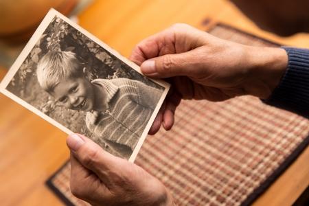 dětství: zblízka z mužských rukou s staré fotografie Reklamní fotografie