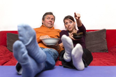 father and daughter on a couch enjoys a movie photo