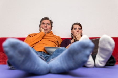 white socks: father and daughter on a couch watching a scary movie Stock Photo