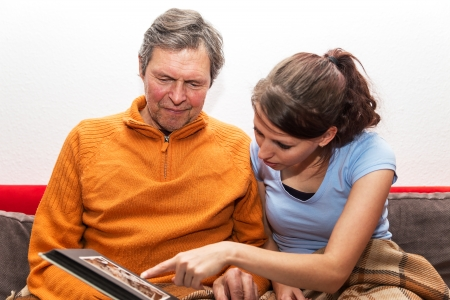 residental care: father and daughter are watching photos