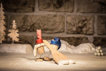 icescape: Concept two men and a snowpusher, wine cork figures Stock Photo