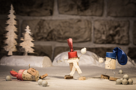 humanly: Concept snowball fight with children, wine cork figures
