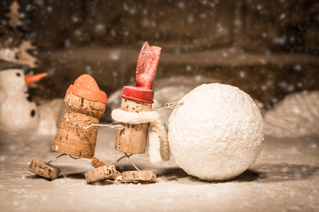 humanly: Concept snowball rolling, wine cork figures Stock Photo