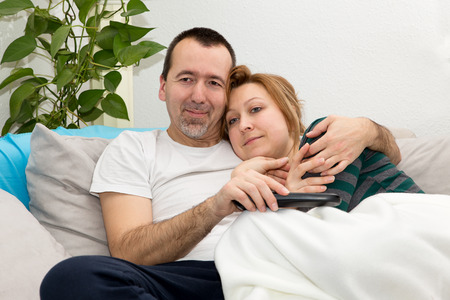 a young Couple watching Tv on a Sofa photo
