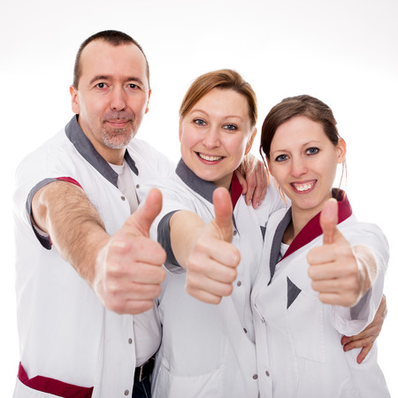 three nurses demonstrate teamwork and success in front of white photo