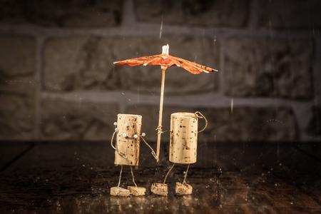 雨の中で概念カップル ワインのコルクの数字 写真素材