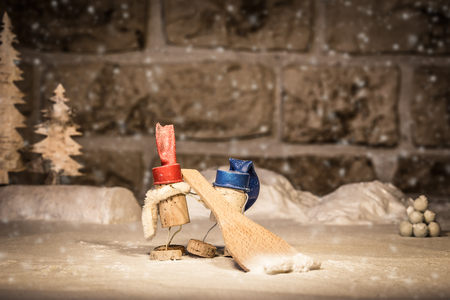 icescape: Concept snow shoveling in the winter of wine cork figures Stock Photo
