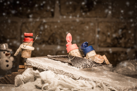 humanly: Concept children sledging in the winter by wine cork figures