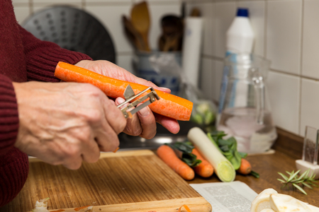 close up, elderly male hands peel vegetables photo