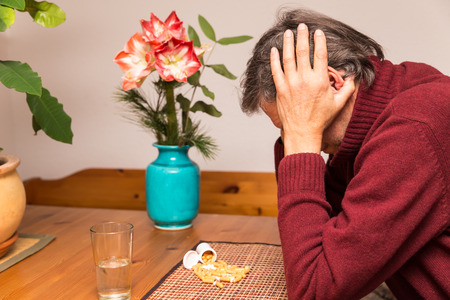 senior depression: close up of a senior adult with tablets