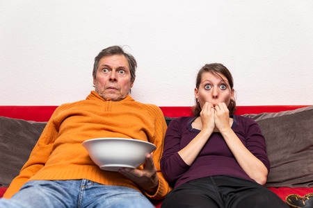 father and daughter on a couch watching a creepy movie photo