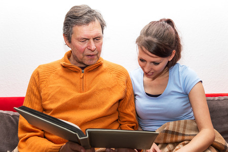 residental care: father and daughter are watching a photo album