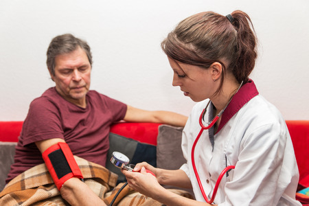 hypotension: doctor and patient checking blood pressure