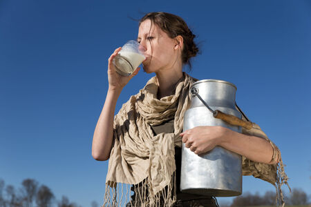 pretty woman is drinking fresh milk in front of blue sky photo
