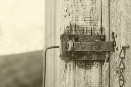 old wooden door with a rusty latch, sepia look photo