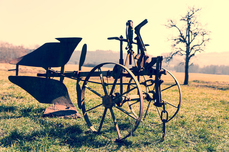 rusty plow in the field with Vintage filter photo