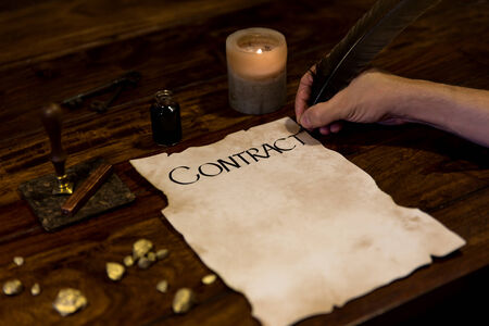medieval man writes a contract with a feather photo