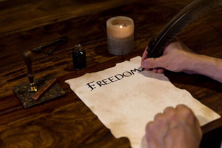 Man writes on parchment the word freedom photo