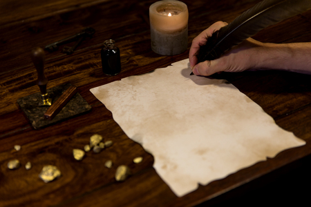 old writing: man writing with a feather on a old parchment Stock Photo
