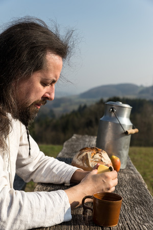 snacking: a bearded man is snacking in the nature Stock Photo