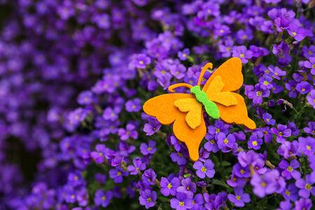 violett: a orange felt butterfly atop a violett lilacbush Stock Photo