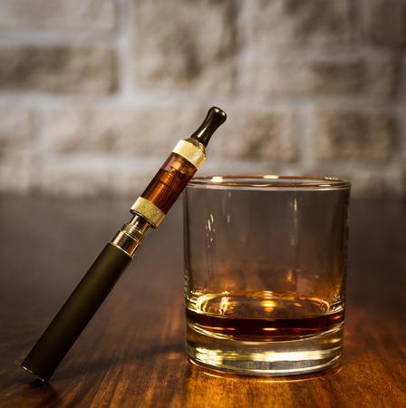 電子タバコとバーボンのガラスのビンテージ静物