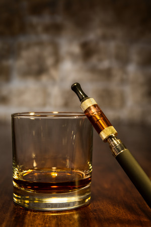 vintage still life with electronic cigarette and a glass of whiskey photo